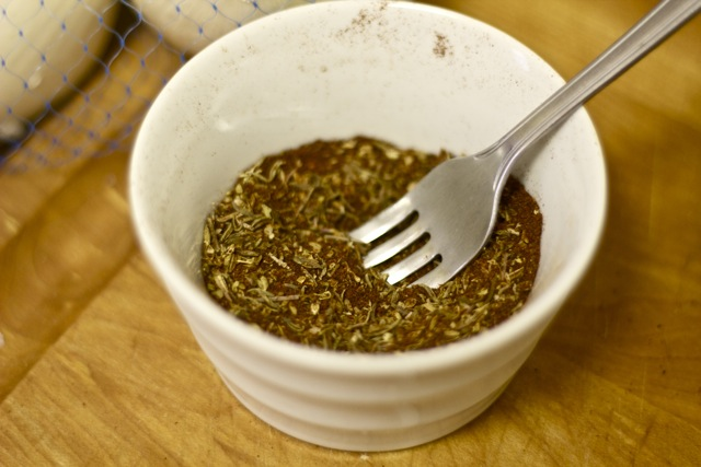Cinnamon, thyme, oregano, chili powder, cumin and chipotle in a bowl with fork